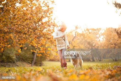 Niña caminando en el parque con su perro