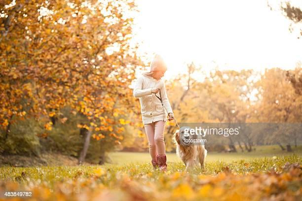 Bambina camminare nel parco con il suo cane