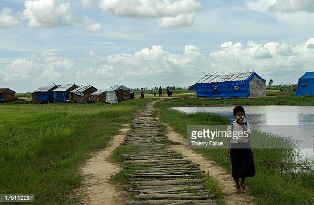 A little girl walks on her way from a temporary school in a village devastated by cyclone Nargis According to official figures the cyclone killed...