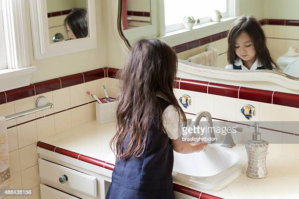 Little girl washing her hands in her home's bathroom