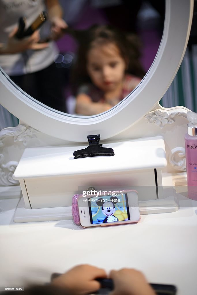 A little girl watches a cartoon displayed on her mother's mobile phone while having her hair prepared during a casting for Babybook magazine on November 10, 2012 in Geneva. More than 1,500 children are expected to participate in Europe's largest children casting, organised in Geneva through November 18 by Swiss glossy magazine Babybook, whose owner, Richard Blat, dreams of creating the first Kids Fashion Week in Qatar. AFP PHOTO / FABRICE COFFRINI