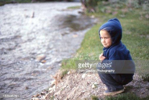 Little girl watching spring creek : Stock Photo