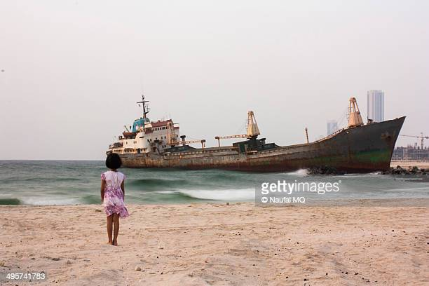 Little girl watching the grounded ship