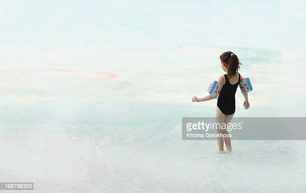 A little girl watching the waves in the pool