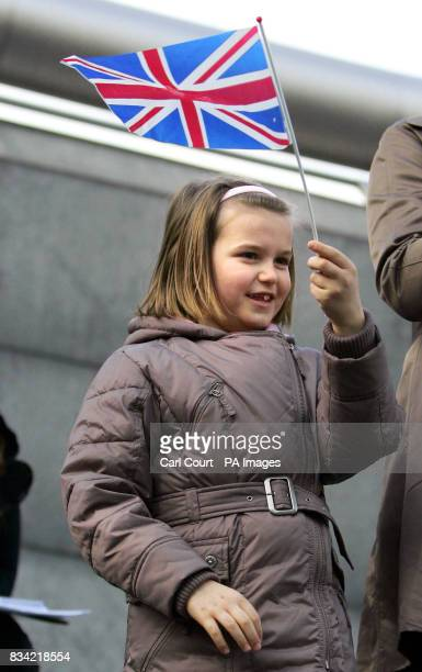 A little girl waves a flag at soldiers of the 151 Transport Regiment as they march towards City Hall where they will receive medals for services in...