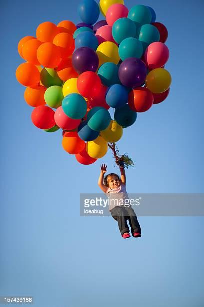 Petite fille Agiter les mains en montgolfières transporter son vol de loin