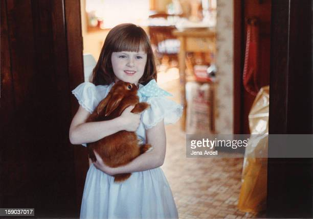Little Girl Wearing a Dress Holding a Bunny Rabbit