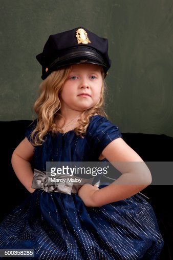 Little girl wearing a police officer's hat.