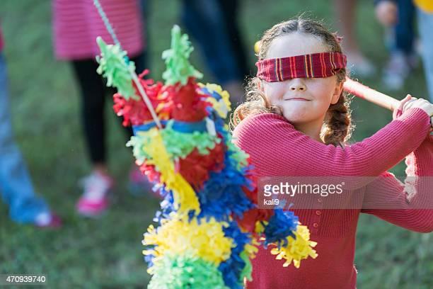 Kleines Mädchen mit Augenbinde schlagen eine Piñata