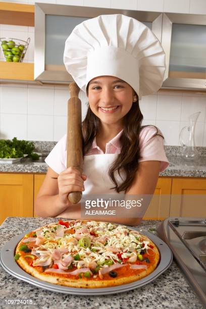 Little Girl Wearing Chefs Hat Holding Rolling Pin with Pizza