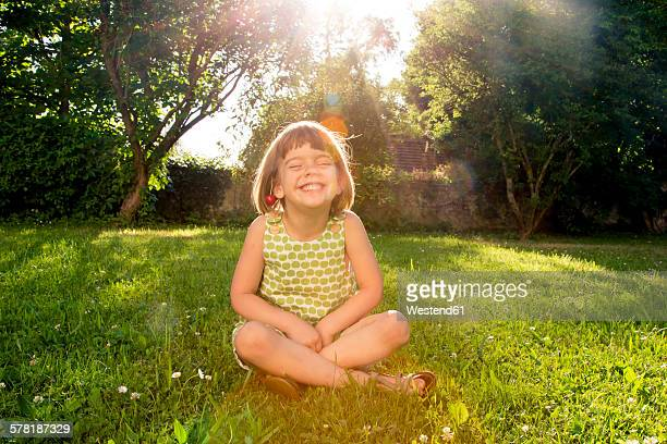 Little girl wearing cherries sitting on a meadow at backlight