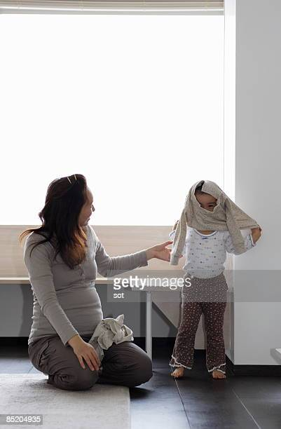Little girl wearing clothes with pregnant mother