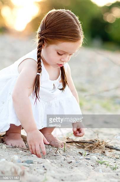 Petite fille portant une robe à la recherche dans le sable sur la plage