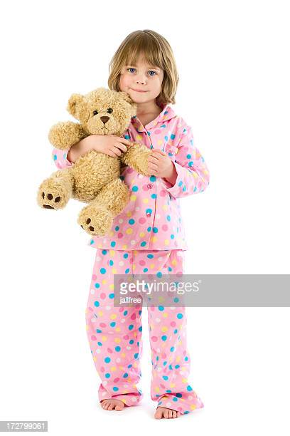 Little girl wearing pyjamas holding teddy on white