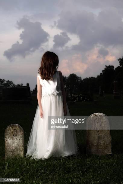 Kleines Mädchen mit weißem Kleid in Friedhof