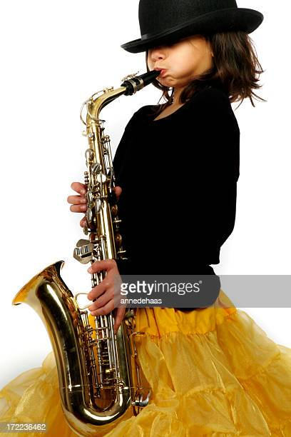 Little girl wearing yellow skirt playing the saxophone