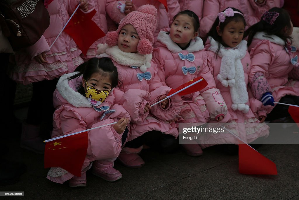 A little girl wears the cartoon mask at the Tiananmen Square during severe pollution on January 29, 2013 in Beijing, China. The 4th dense fog envelops Beijing with pollution at hazardous levels in January.