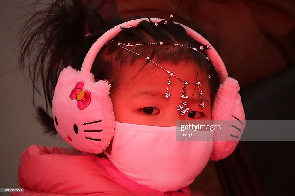 A little girl wears the mask during severe pollution at Tiananmen Square on January 30, 2013 in Beijing, China. The fourth round of heavy smog to hit Beijing in one month has sent more people to the hospital with respiratory illnesses and prompted calls for legislation to curb pollution. The haze choking many Chinese cities covers a total area of 1.3 million square kilometers, the China's Ministry of Environmental Protection said Tuesday.