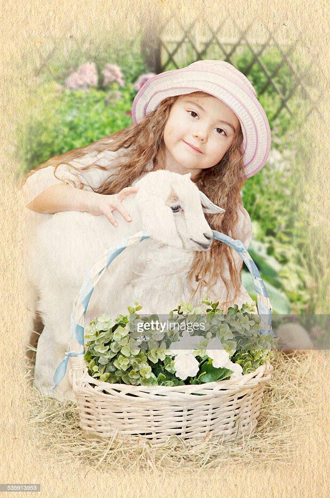 Niña con un bebé de cabra : Foto de stock