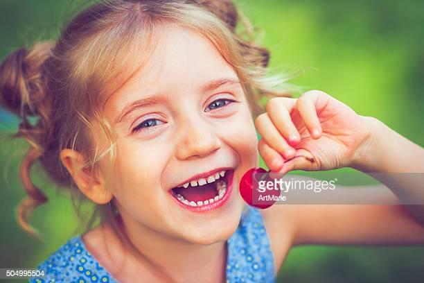 Kleines Mädchen mit einer Kirsche