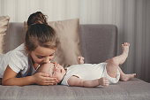 A little girl five years old,a brunette,dressed in a white shirt and white pants,spends time together with her newborn brother,three-month-old boy,dressed in a white t-shirt and white panties,at home