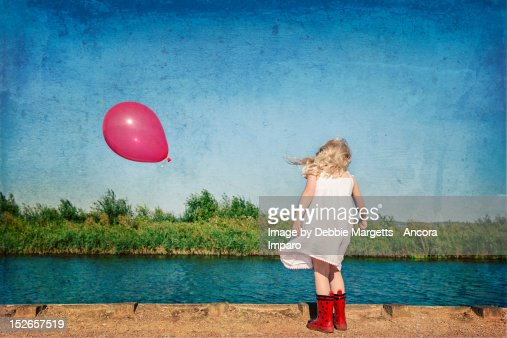 Little girl with a red balloon spotting river fish : Stock Photo