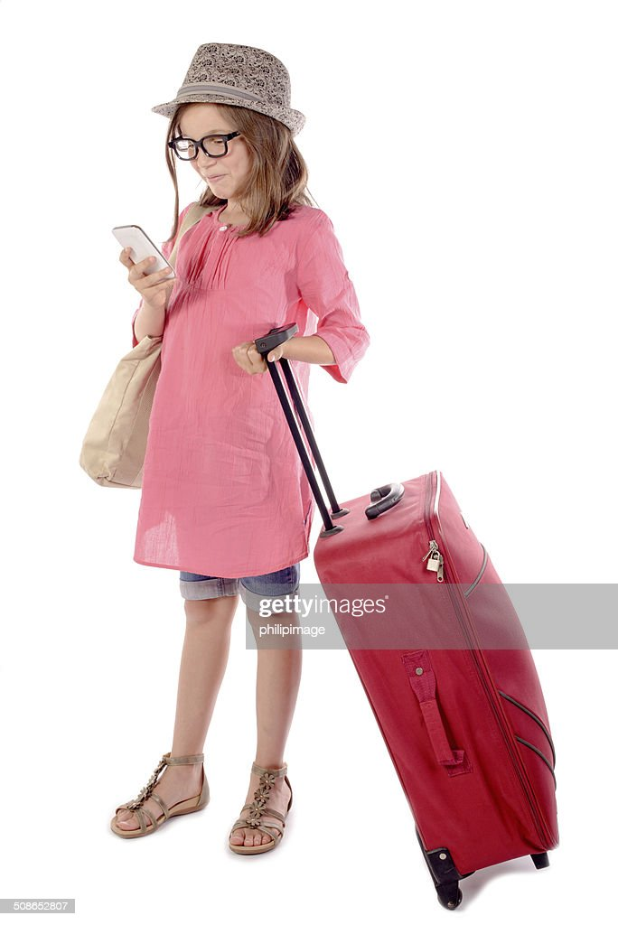 little girl with a red suitcase talking on phone : Stock Photo