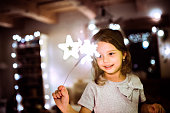 Beautiful little girl with a sparkler at Christmas time at home.