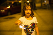 Little girl with a sparkler at night to celebrate the festivity of Sant Joan on a street in Barcelona, Catalonia, Spain