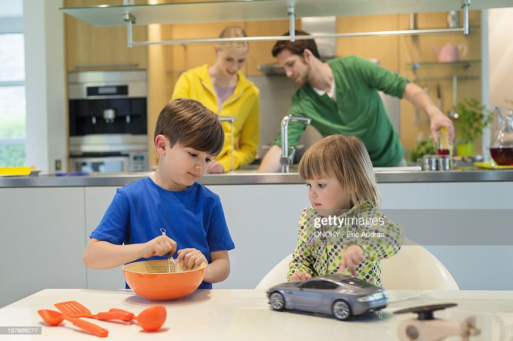 Little girl with a toy car looking at his brother cooking in the kitchen