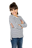 Portrait of little happy girl in striped t-shirt and blue jeans standing with arms crossed. Isolated on white