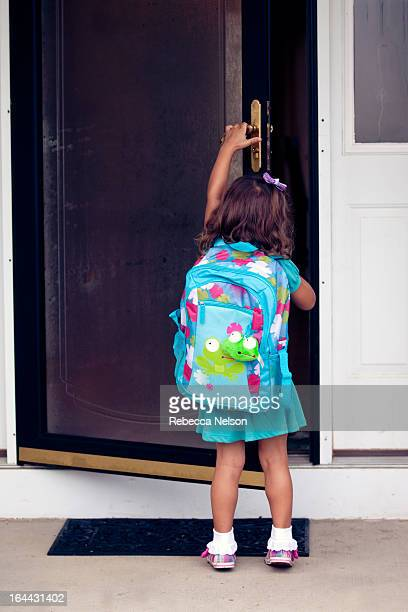 Little girl with backpack opening front door