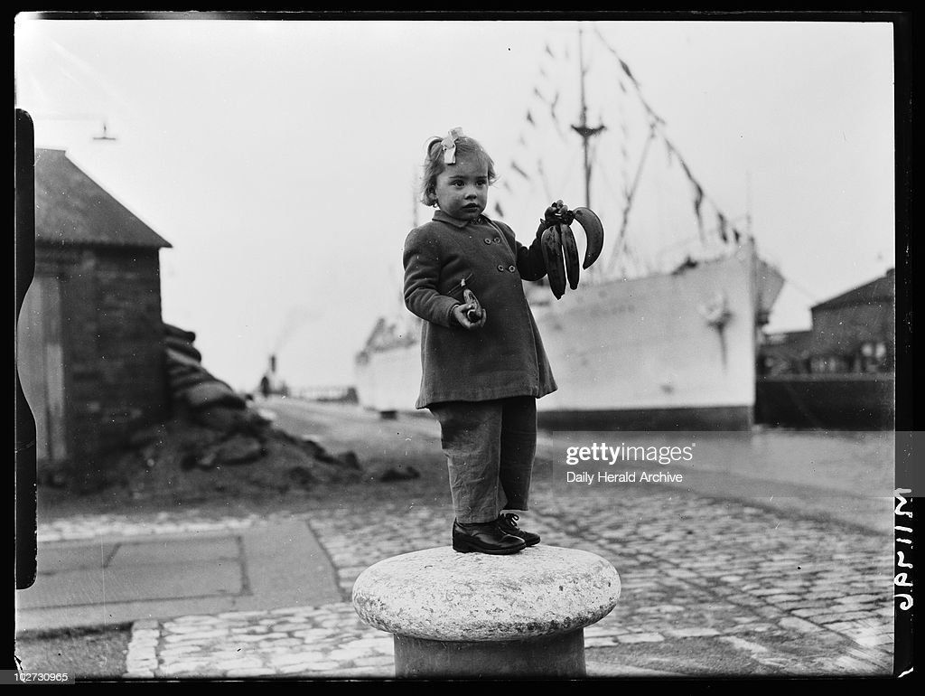 Little girl with bananas, 1945 A photograph of a little girl standing on a bollard at Avonmouth Dock holding a bunch of bananas, taken by Smith for the Daily Herald newspaper on 30 December, 1945. This lucky little girl, Zoya Smith, holds some of the first bananas imported into Britain after the end of World War Two. This fruit came from the SS Tilapa, docked at Avonmouth Dock in Bristol. During the war most foodstuffs were rationed, especialy those brought from overseas. Rationing did not officially end in Britain until 1954. This photograph has been selected from the Daily Herald Archive, a collection of over three million photographs. The archive holds work of international, national and local importance by both staff and agency photographers.