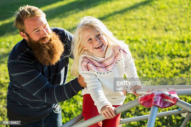 Little girl with blond hair on playground with father
