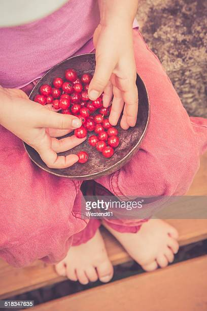 Little girl with bowl of red currants, partial view