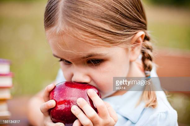 Petite fille mangeant une pomme avec Natte