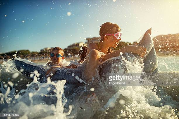 Little girl with brothers having fun in sea