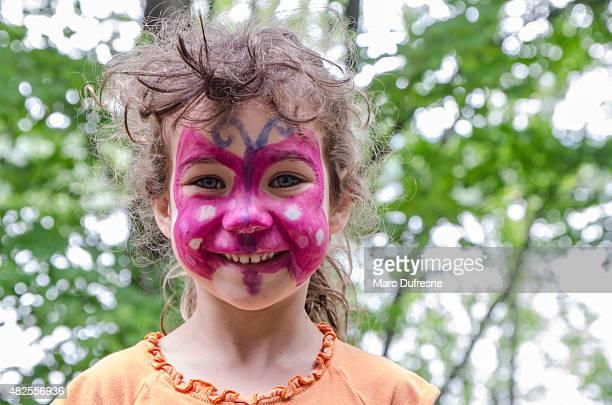 Kleines Mädchen mit einem Schmetterling auf Ihr Gesicht gemalt