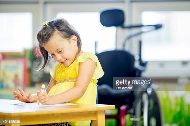 Little Girl with Cerebral Palsy Coloring at School
