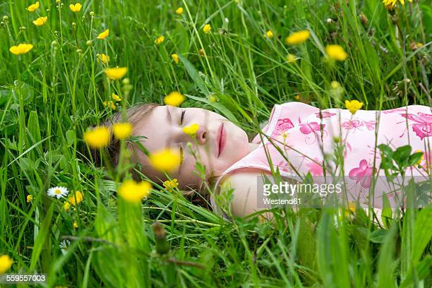 Little girl with closed eyes lying on a flower meadow