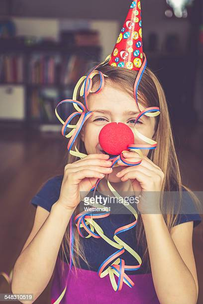Little girl with clowns nose and cap blowing streamer