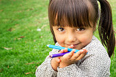 Horizontal close up portrait of 4 year old girl holding color pencils looking at the camera and smiling.