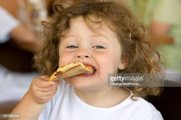Little girl with curly hair biting into a slice of pizza