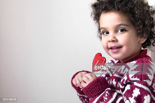 Little girl with curly hair holding a heart shaped lollipop