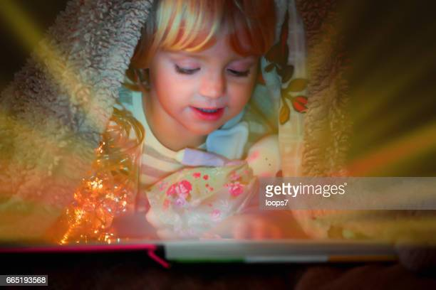Little Girl with Digital Tablet under the Blanket