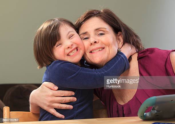 Little girl with Down Syndrome hugging her Mom