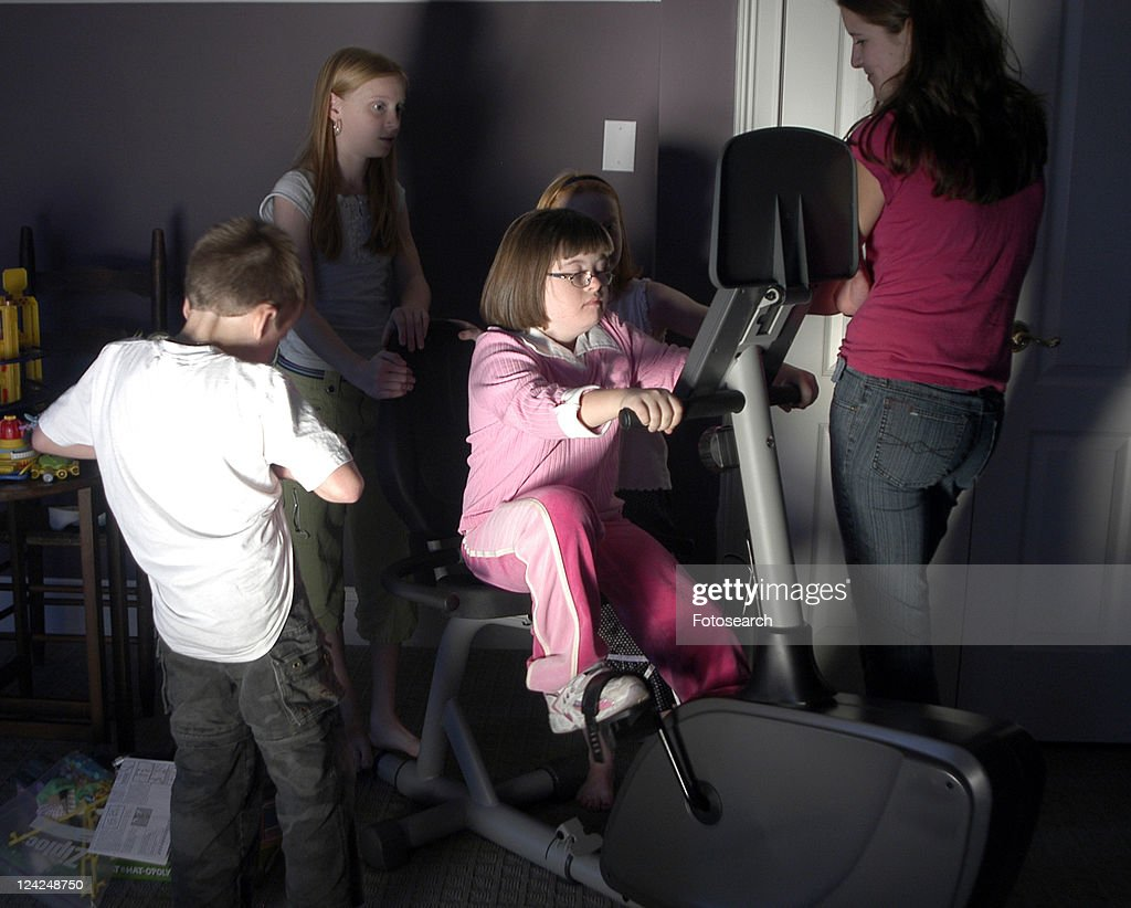 Little girl with Down Syndrome taking a turn on some exercise equipment. : Stock Photo