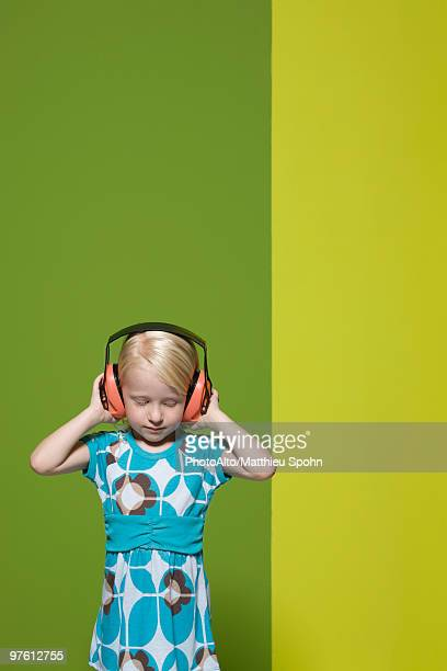 Little girl with eyes closed wearing protective headphones