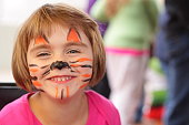 """little girl smiles at camera, face painted like tiger"""