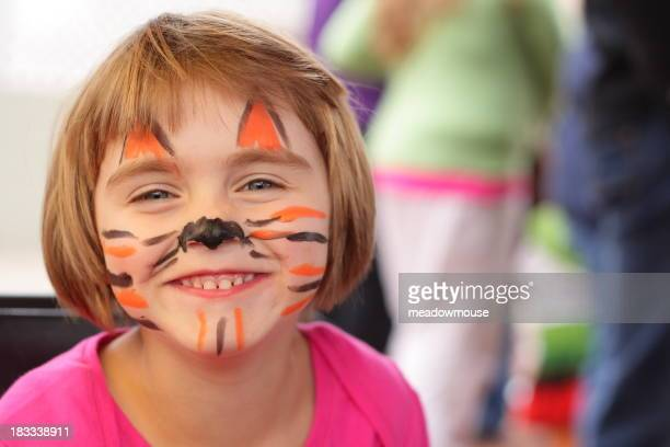 Little girl with face painted like tiger smiles at camera